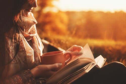 Una donna legge un libro e tiene una tazza