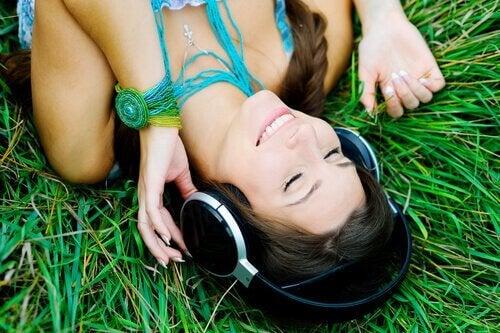 Ragazza distesa sull'erba ascolta la musica con le cuffie