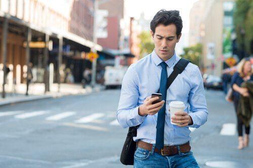 Smartphone zombie, uomo che cammina fissando il cellulare