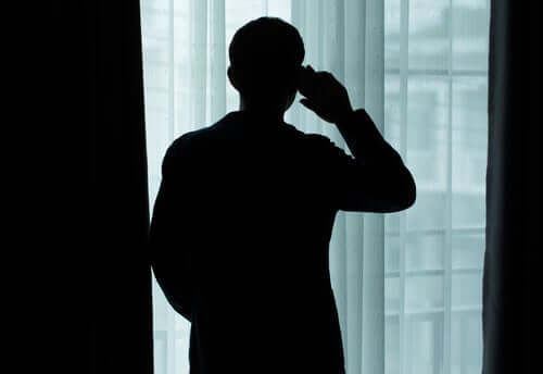 Uomo parla al telefono davanti alla finestra allo altro capo