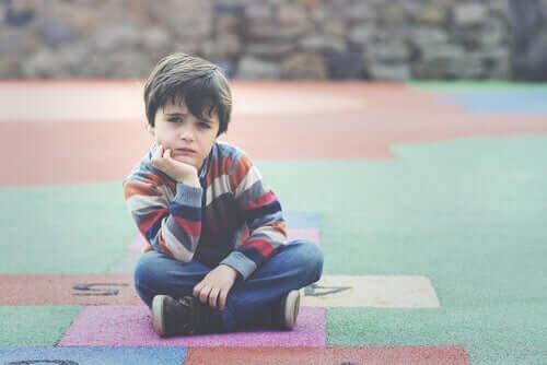 Bambino pensieroso seduto a terra