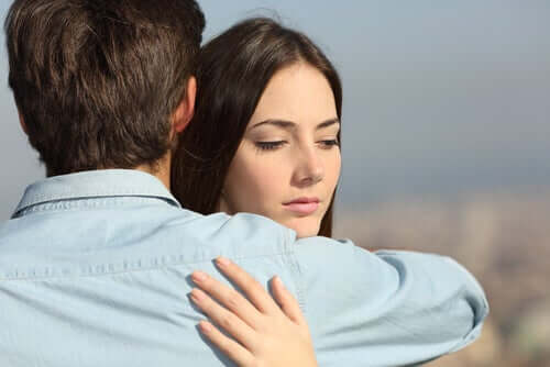 Donna pensierosa abbracciata al partner