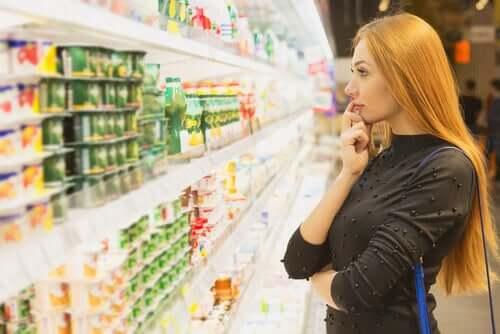 Donna che riflette su quale yogurt comprare