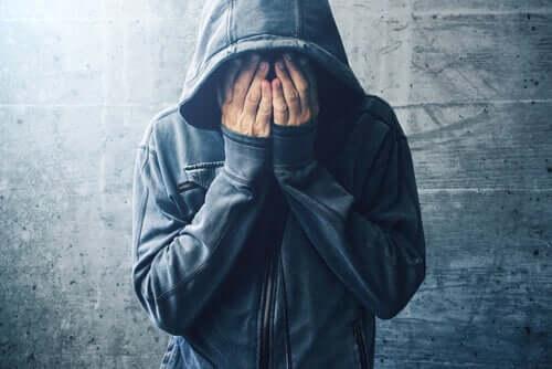 Uomo con cappuccio che si copre il volto con le mani