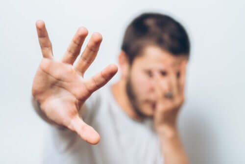Uomo che ha paura con la mano davanti alla faccia