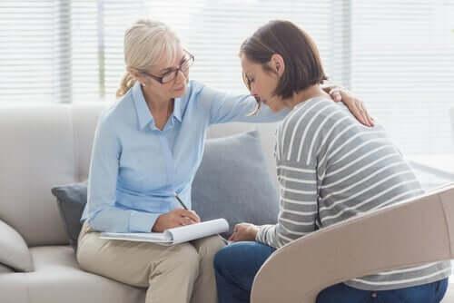 Psicologa con mano sulla spalla della paziente mentre mostra le sue abilità terapeutiche
