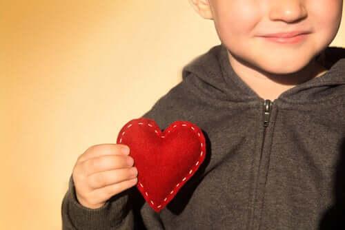 Bambino con cuore di stoffa in mano come simbolo dello sviluppo emotivo dei bambini