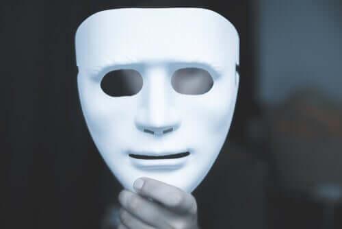 Mano che sorregge una maschera bianca