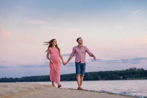 Ragazzo e ragazza si tengono per mano in spiaggia