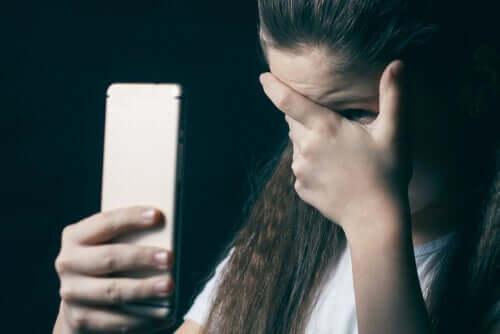 Bambina con il cellulare che si copre gli occhi perché vittima di child grooming