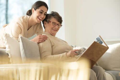 Infermiera con donna anziana che guardano un album fotografico