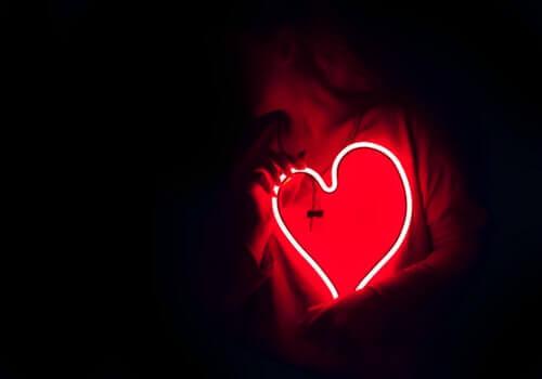 Donna con neon a forma di cuore