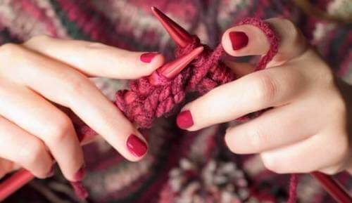Mani che intrecciano la lana