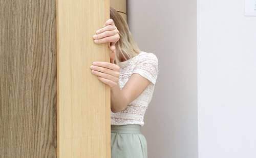 Ragazza che si nasconde dietro un muro