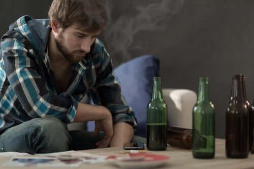 Ragazzo con bottiglie di vino sul tavolo che segue un trattamento della dipendenza da alcool