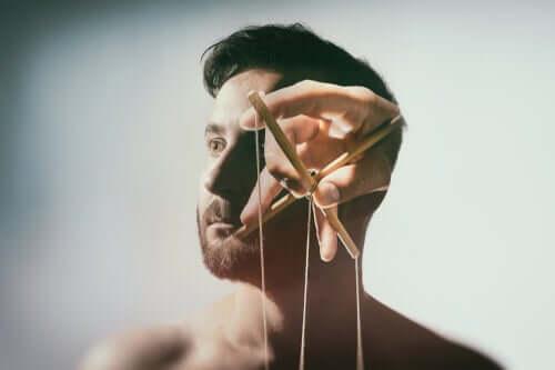 Testa di uomo manipolata da fili da marionetta