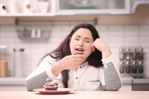 Donna seduta in cucina che mangia un dolce