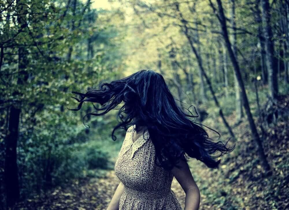 Donna che scappa in mezzo al bosco