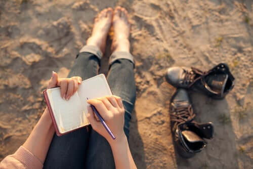 Donna che scrive su un taccuino seduta sulla sabbia