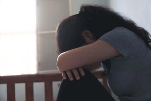 Donna seduta con testa tra le braccia e disturbi dello umore