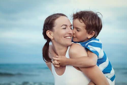 Bambino a cavalcioni sulla mamma in spiaggia
