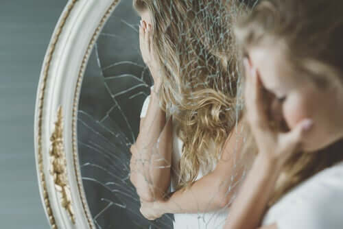 Ragazza triste con le mani sul volto di fronte a uno specchio rotto