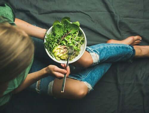Giovane donna che mangia delle verdure