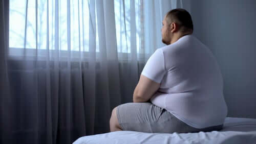 Uomo obeso seduto sul letto