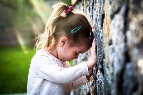 Bambina triste appoggiata a un muro