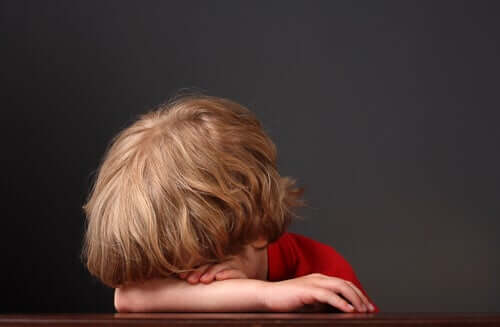 Bambino triste che nasconde il viso