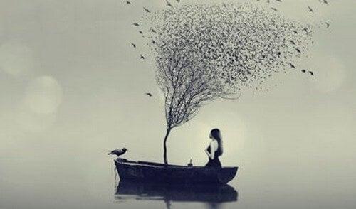 Donna in barca e albero spoglio in mezzo al mare