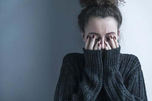 Ragazza schizofrenica con le mani sul volto