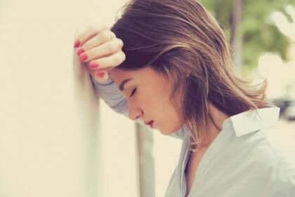 Donna con la testa appoggiata sul muro
