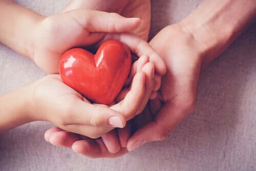 Quattro mani sorreggono un cuore
