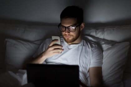 Ragazzo a letto con cellulare e computer