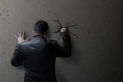 Uomo furioso che sbatte il pugno contro il muro