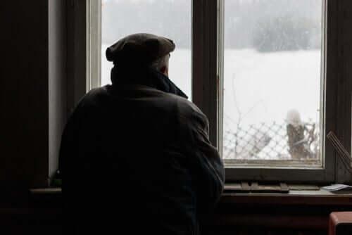 Uomo anziano di spalle che guarda dalla finestra