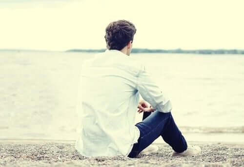 Uomo da solo sulla spiaggia che ha deciso di abbandonare il cellulare
