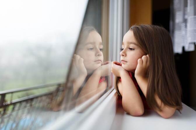 Bambina che guarda fuori dalla finestra