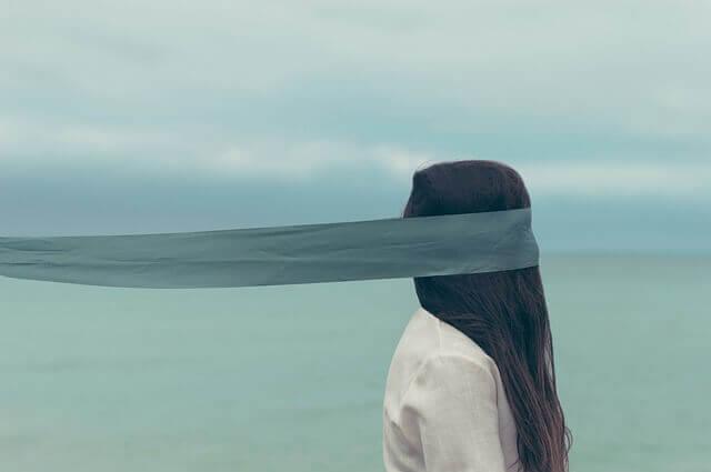 Donna bendata in cerca della soluzione al conflitto interiore