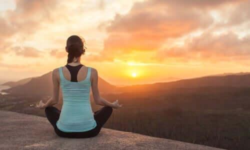Donna che medita guardando il tramonto