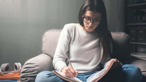 Ragazza con occhiali che studia seduta sulla poltrona