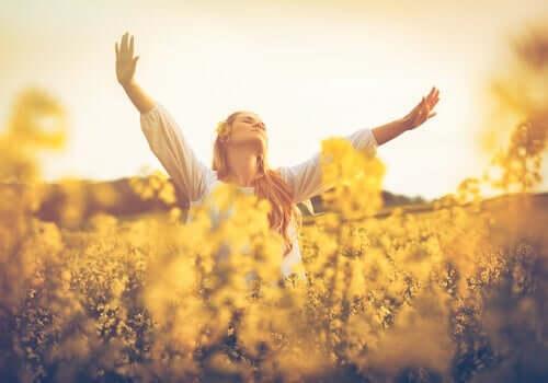 Ragazza felice che balla in mezzo ai fiori in campagna