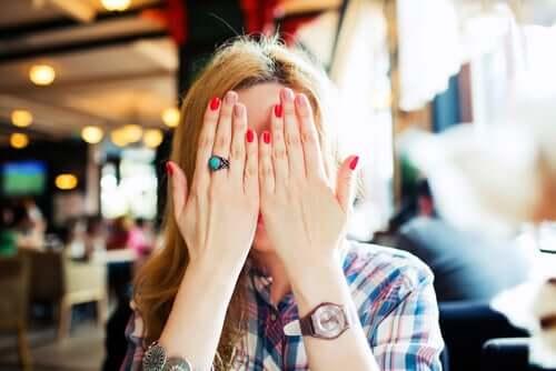 Donna che si copre il viso dalla vergogna