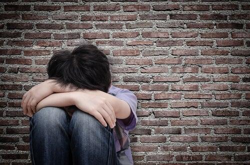 Bambino triste accovacciato da solo con la testa tra le braccia