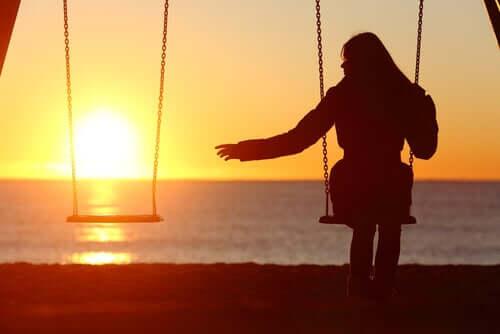 Donna sola sull'altalena al tramonto che vuole trovare un partner