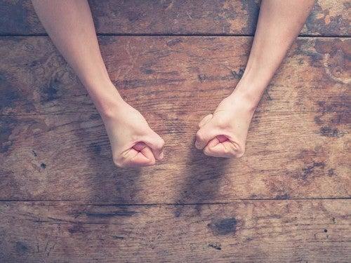 Pugni chiusi sul tavolo come simbolo del paradigma del transfer di eccitazione