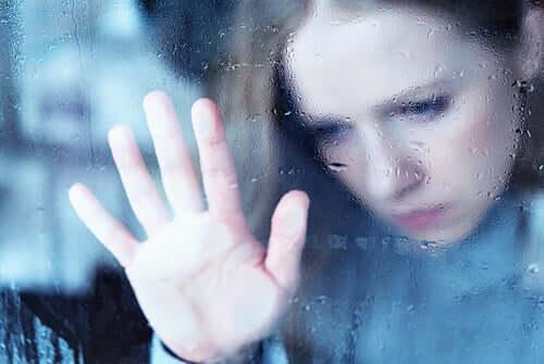 Ragazza triste con la mano appoggiata al vetro
