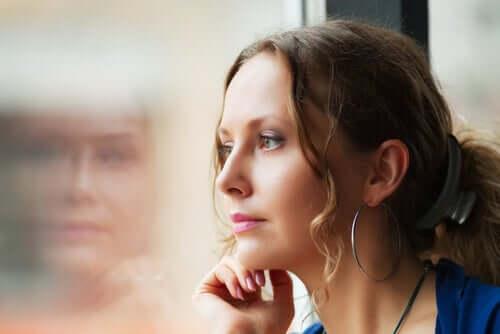 Donna pensierosa che guarda dalla finestra