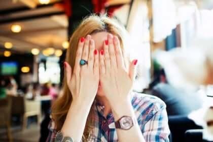 Donna che si copre il viso per la vergogna